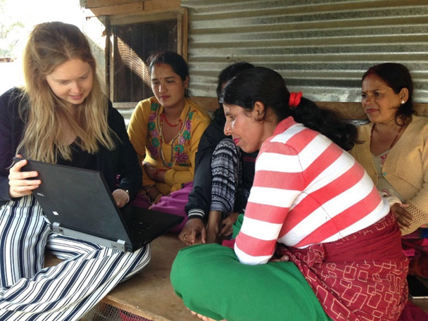 Volunteer giving computer lessons to women